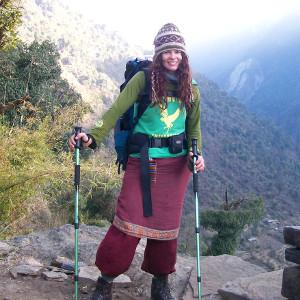 Elisa mit Rucksack und Trekkingstöcken.