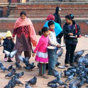 Tauben fütternde Frauen und Kinder